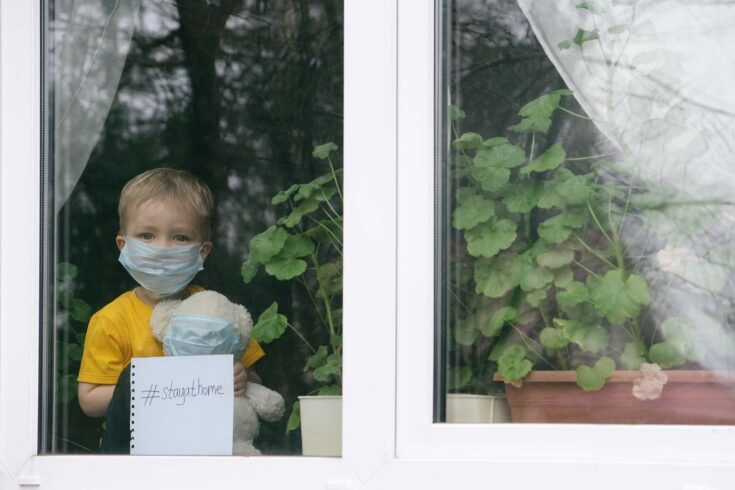 Child in face mask looking out from behind closed window