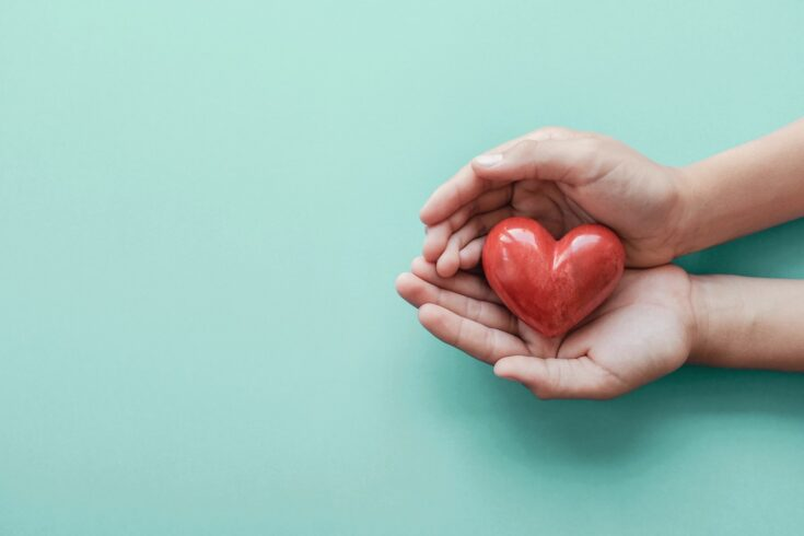 hands holding red heart on blue background, health care, love, organ donation, family insurance and CSR concept, world heart day, world health day