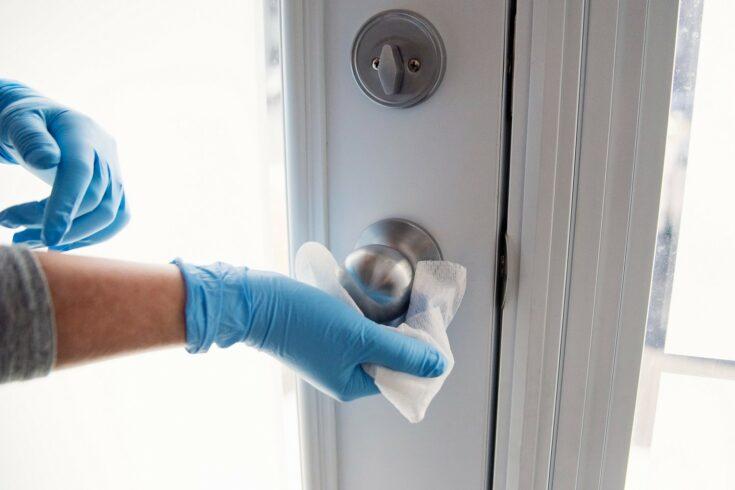 Gloved hands cleaning a door handle