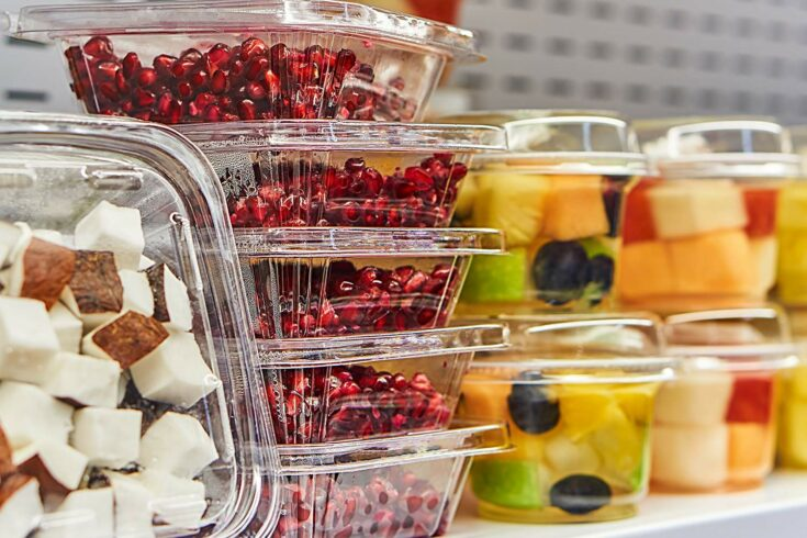 Fruit in plastic containers on supermarket shelf