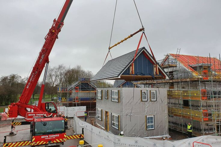 Construction crane lowering roof onto house. Credit: AIMCH.