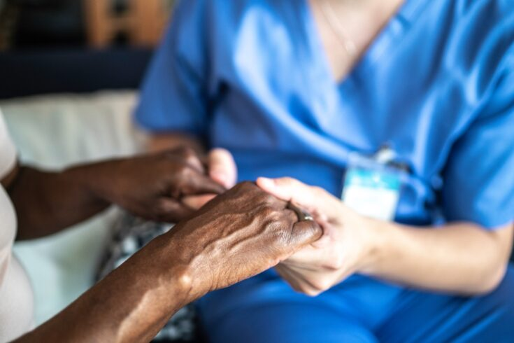 Close-up of healthcare worker and senior woman holding hands