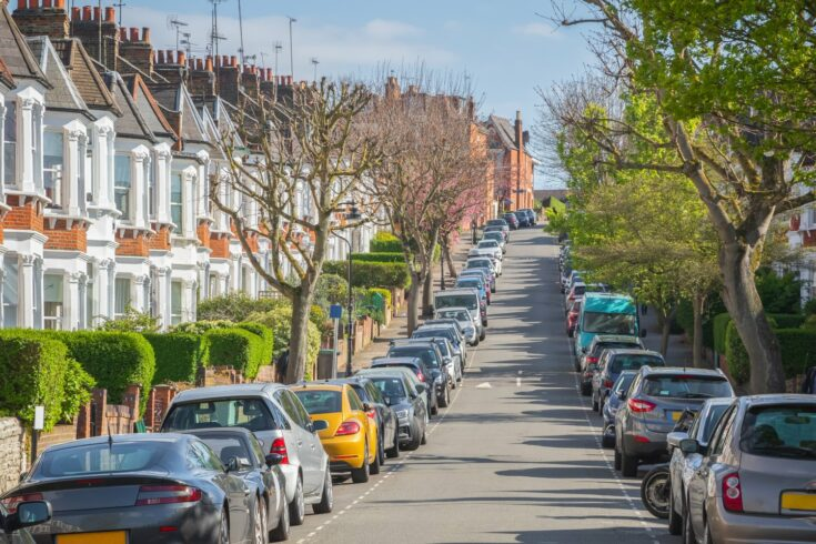 Typical London street lined with terraced houses and parked cars
