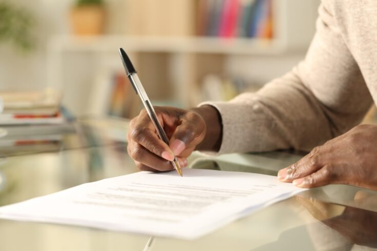 Close up of black man hands signing document on a desk