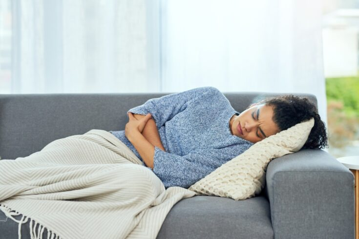 Woman unwell lying on a sofa with a blanket