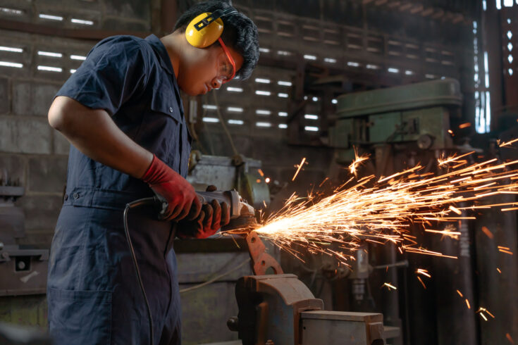 Asian Mechanical engineer operating power tools with metal sparks