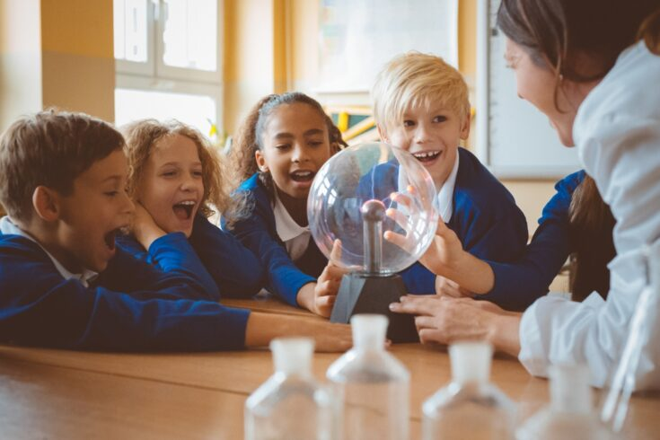 Group of school kids listening to female teacher showing plasma ball during physics lesson