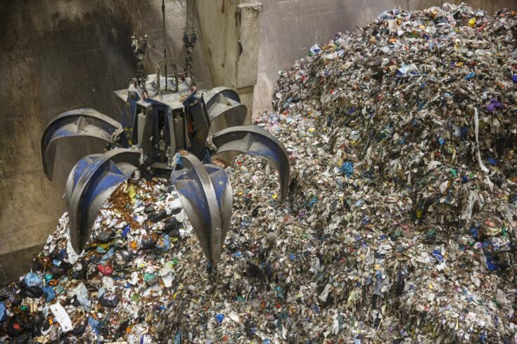 Mechanical claw hand grabbing pile of mixed waste