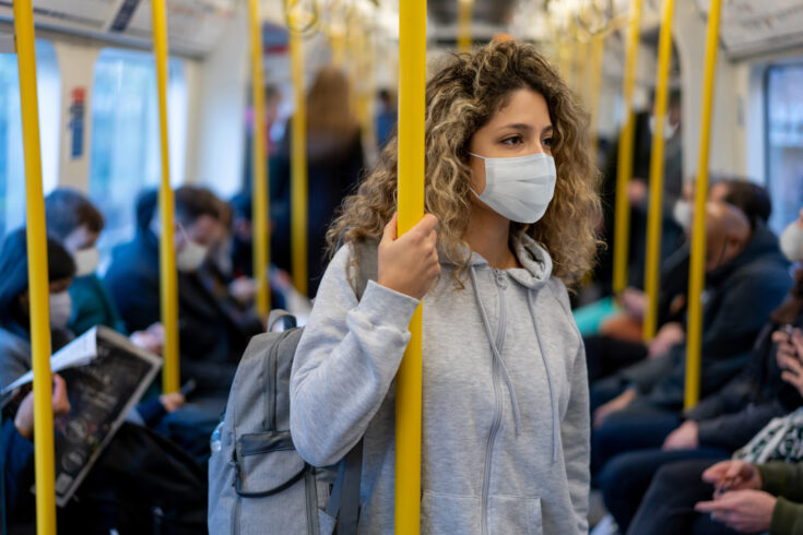 Woman riding on the metro wearing a facemask to avoid an infectious disease