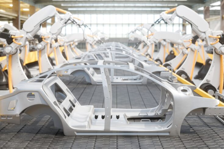 Industrial welding robots at the automated car manufacturing factory assembly line