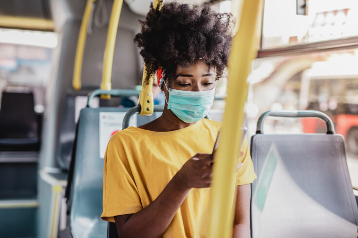 Young black woman sitting on the bus and wearing a protective mask and using a mobile phone
