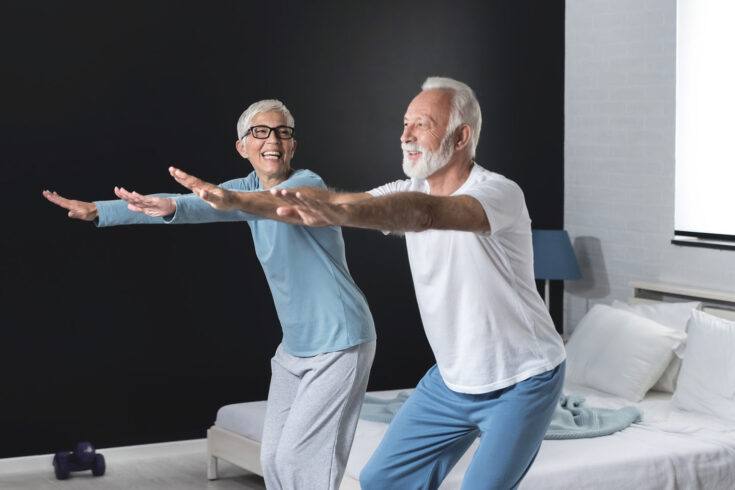 Portrait of happy senior couple performing exercise at home.