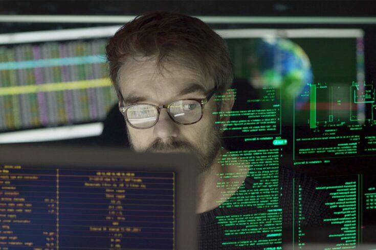 Man coding, computer screens