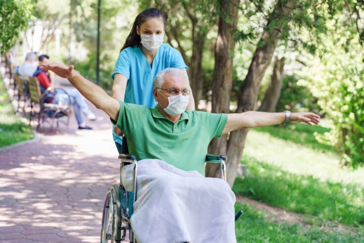 Young female nurse with disabled man in the garden