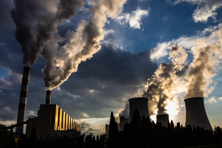 View of the smoking chimneys of a coal-fired power plant against the backdrop of a dramatic sky with clouds