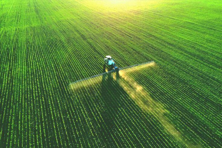 Tractor spraying fertiliser on green field