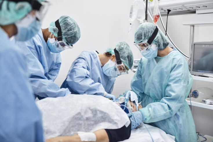 Team of Doctors and Nurses Operating Male Patient