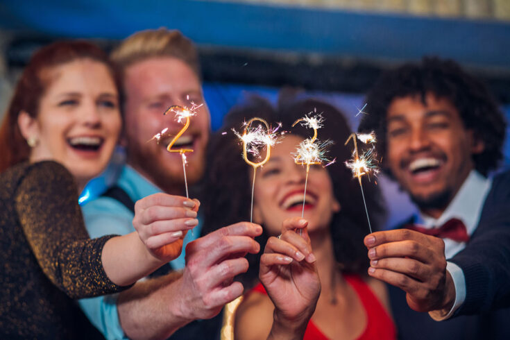 Joyful young people holding sparklers in a club.