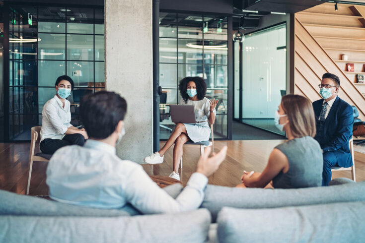 Group of entrepreneurs, wearing masks, sitting at a distance in the office and talking.