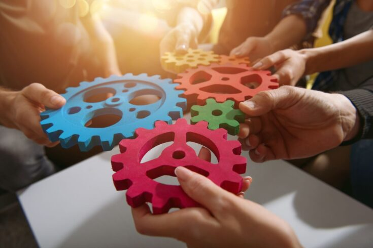 Team working, connecting pieces of gears