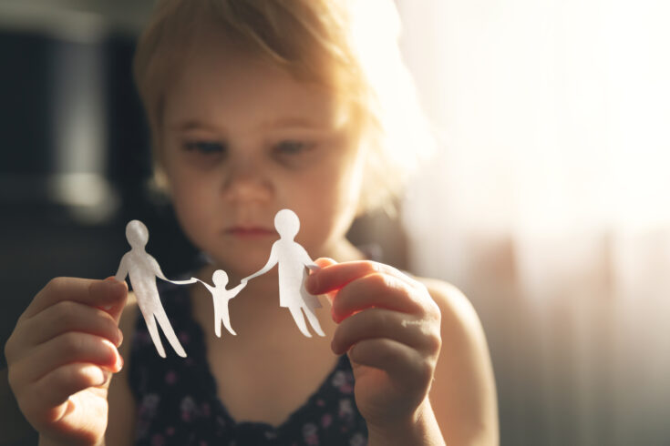 Little girl with paper family in hands