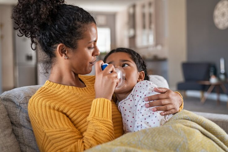 A mother embracing daughter making inhalation with a nebulizer