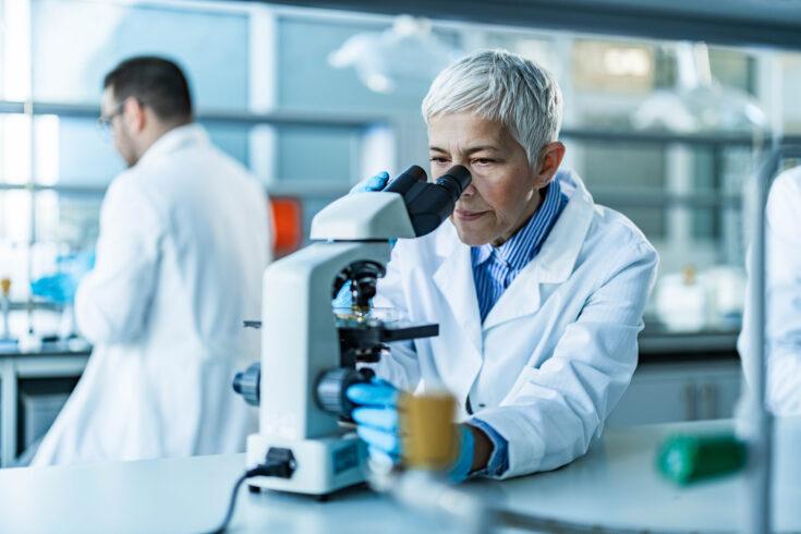 Senior female scientist working on a microscope in laboratory
