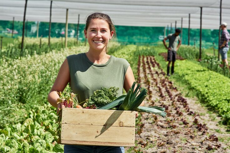 Female farmer holding box of produce