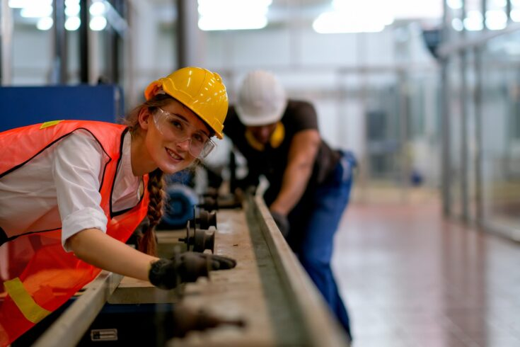 Female technician smile and look forward in front of rail of the machine with her co-worker as background in factory