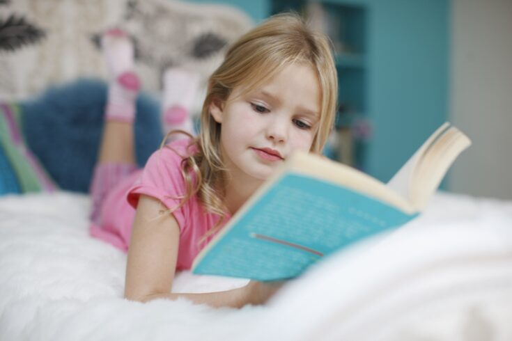 Girl lying on bed reading book