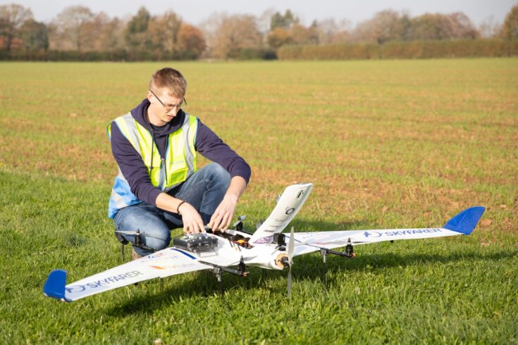 Man with autonomous drone in a field