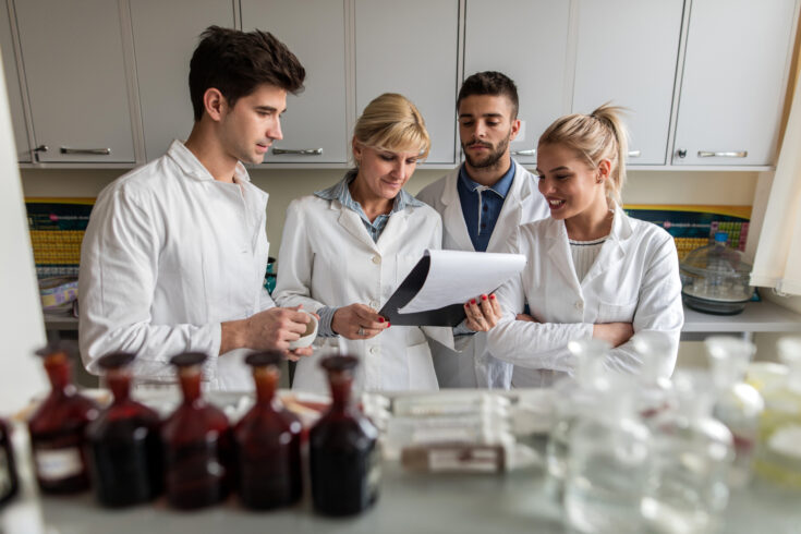 Team of four doctors in laboratory reading medical report.