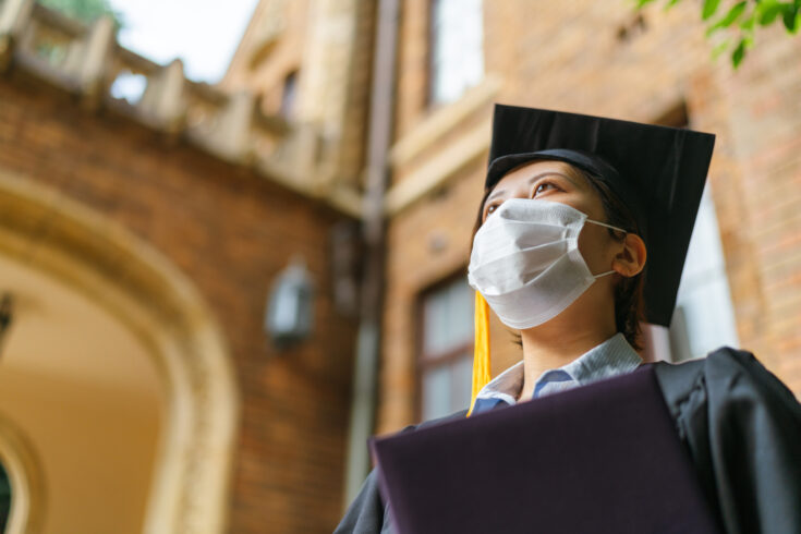 Low angle portrait of student in graduate gown with diploma